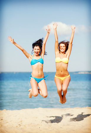 chill out: summer holidays and vacation - girls jumping on the beach