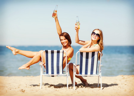 summer holidays and vacation - girls sunbathing and drinking on the beach chairs