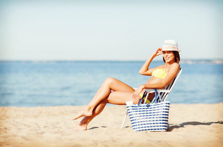 strandstoel: summer holidays and vacation - girl sunbathing on the beach chair Stockfoto