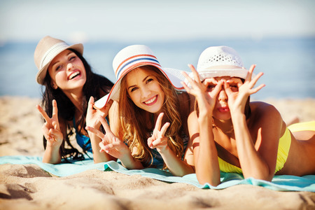 friends party: summer holidays and vacation - girls sunbathing on the beach Stock Photo