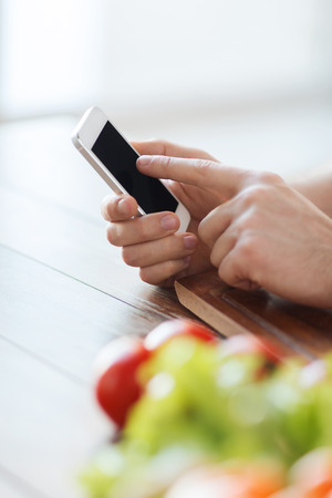 cooking, technology and home concept - closeup of male hand pointing finger to smartphone photo