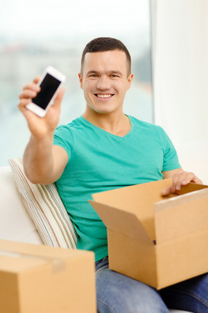 recieve: post, home, technology and lifestyle concept - smiling man opening cardboard box with smartphone in it