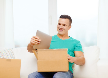 recieve: post, home, technology and lifestyle concept - smiling man opening cardboard box with tablet pc computer in it Stock Photo