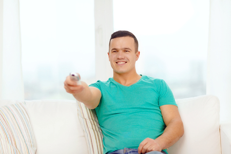 home, technology and entretainment concept - smiling man with tv remote control at home photo