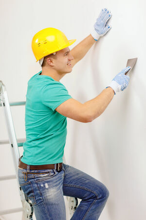 tinkering: repair, renovation and home concept - smiling man in helmet doing renovations at home Stock Photo