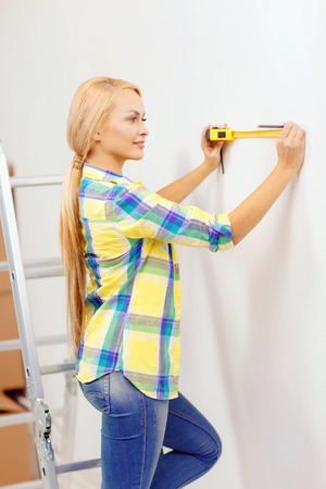 repair, building and home concept - smiling woman measuring wall photo