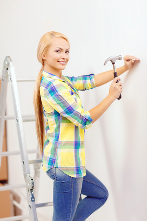 reapir, building and home renovation concept - smiling woman hammering nail in wall photo