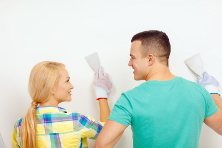 repair, renovation and home concept - smiling couple doing renovations at home and looking at each other photo
