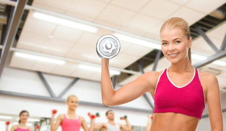 fintess, healthcare and dieting concept - young sporty woman with heavy steel dumbbell photo