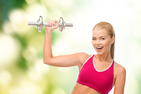 strong arm: fintess, healthcare and dieting concept - young sporty woman with heavy steel dumbbell