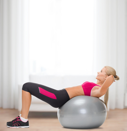 fitness, healcare and dieting concept - young woman doing exercise on fitness ball photo