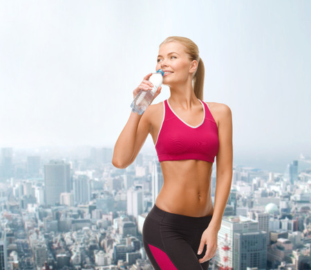 fitness, healthcare and dieting concept - smiling sporty woman with bottle of water photo