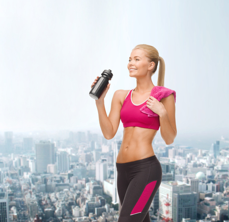 fitness, healthcare and dieting concept - smiling sporty woman drinking water from sportsman bottle photo