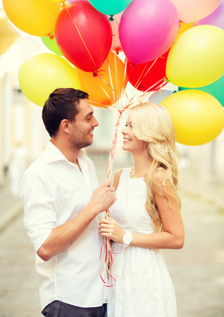 summer holidays, celebration and dating concept - couple with colorful balloons in the city photo