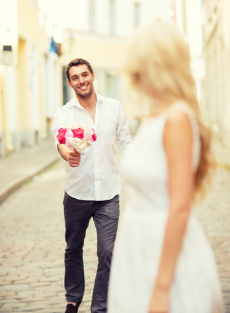 giving season: summer holidays and dating concept - couple with bouquet of flowers in the city