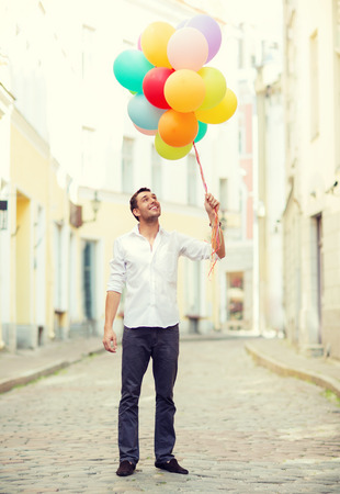 graduation party: summer holidays, celebration and lifestyle concept - man with colorful balloons in the city
