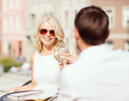 summer holidays and dating concept - woman drinking wine with man in cafe in the city photo