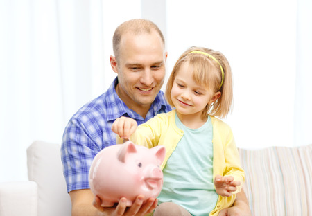 finance girl: family, children, money, investmen and happy people concept - happy father and daughter with big pink piggy bank Stock Photo