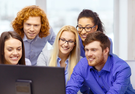 business, office, technology and startup concept - smiling business team looking at computer monitor at office photo