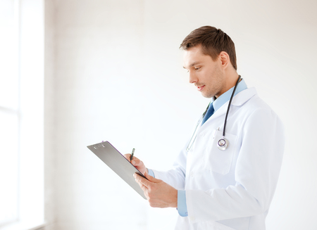 healthcare and medical concept - smiling male doctor with stethoscope and clipboard in hospital photo