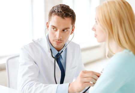 healthcare and medical concept - concentrated male doctor with stethoscope listening to the patient in hospital photo