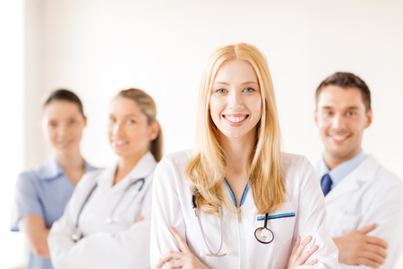 healthcare and medicine concept - attractive female doctor or nurse in front of medical group in hospital photo