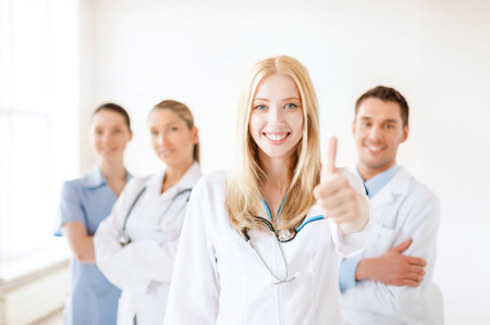 physiotherapists: healthcare and medicine concept - attractive female doctor or nurse in front of medical group in hospital showint thumbs up Stock Photo