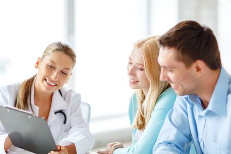 Pacjent: opieki zdrowotnej i koncepcji medycznej - uśmiechnięta kobieta lekarza z schowka i pacjentów w szpitalu