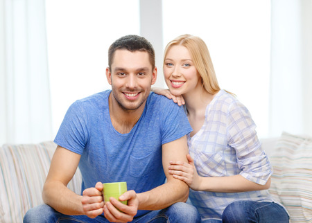 love, family, healthy food and happiness concept - smiling man with cup of tea or coffee with wife or girlfriend at home photo