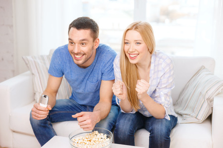 food, love, family, sports, entertainment and happiness concept - smiling couple with popcorn cheering sports team at home photo