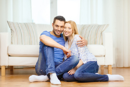 love, family and happiness concept - smiling happy couple sitting on floor at home photo