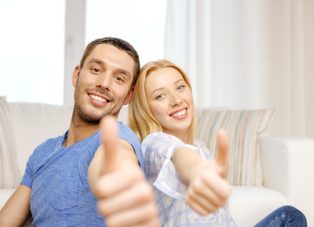 love, family and happiness concept - smiling happy couple at home showing thumbs up photo