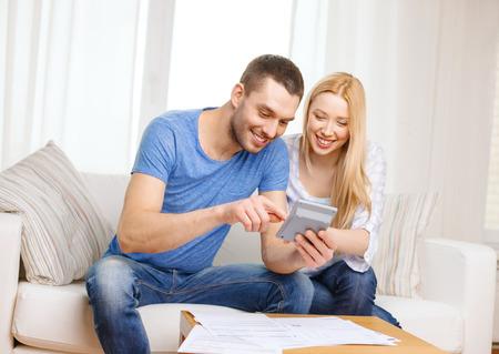 税金、財政、家族、家および幸福のコンセプト - 論文や自宅で電卓とカップルの笑みを浮かべて