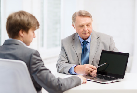 business, advertisement, technology and office concept - older man and young man with laptop computer in office photo