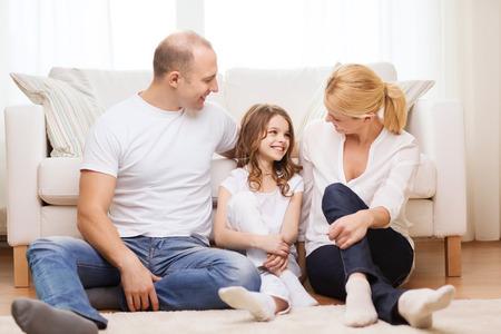 padres hablando con hijos: familia, niño y concepto de hogar - sonriendo padres y la niña sentada en el suelo en casa