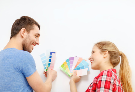 sampler: repair, interior design, building, renovation and home concept - smiling couple looking at color samples at home