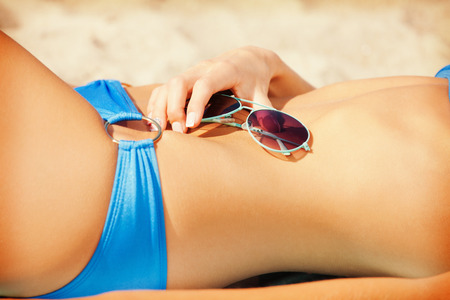 releaxed: closeup picture of female belly, bikini and shades Stock Photo