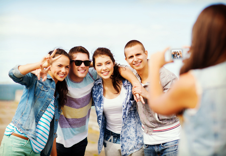 group picture: summer holidays and technology concept - group of teenagers taking photo outside