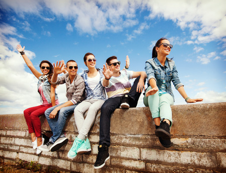 teenagers laughing: summer holidays and teenage concept - group of teenagers hanging out outside