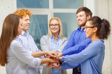agreeing: business, office, gesture and startup concept - smiling creative team with hands on top of each other sitting in office Stock Photo