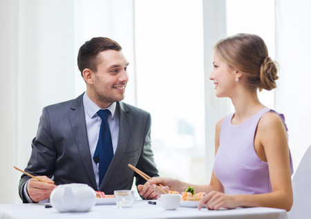 restaurant, couple and holiday concept - smiling couple eating sushi at restaurant photo