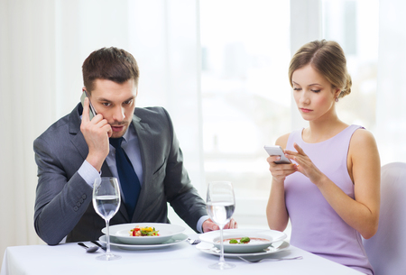 busy restaurant: restaurant, couple, technology and holiday concept - busy couple with smartphones at restaurant