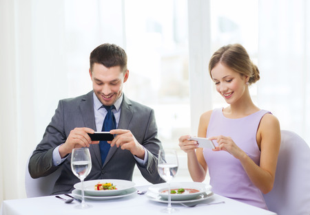 restaurant, couple, technology and holiday concept - smiling couple taking picture of appertizer with smartphone camera at restaurant photo