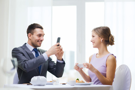 restaurant, couple, technology and holiday concept - smiling man taking picture of wife or girlfriend while picturing sushi with smartphone photo