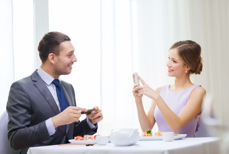 restaurant, couple, technology and holiday concept - smiling woman taking picture of husband or boyfriend while picturing sushi photo