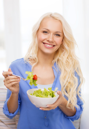 healt, dieting, home and happiness concept - smiling young woman with green salad at home photo