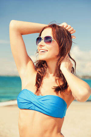 releaxed: picture of happy woman in sunglasses on the beach
