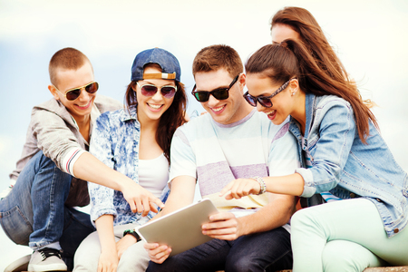 summer holidays, teenage and technology concept - group of teenagers looking at tablet pc photo