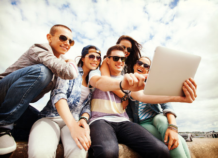 summer holidays, teenage and technology concept - group of teenagers taking picture with tablet pc Stock Photo