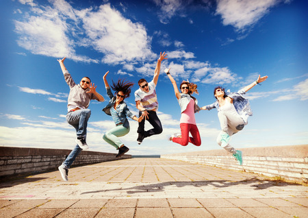 hip hop man: summer, sport, dancing and teenage lifestyle concept - group of teenagers jumping Stock Photo